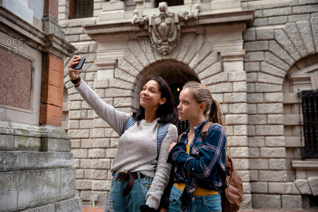 Front view of a Caucasian and a mixed race girl enjoying time hanging out together on a sunny day, standing on the sidewalk, girl taking selfie of herself and her friend.