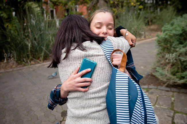 Front view of a Caucasian and a mixed race girl enjoying time hanging out together on a sunny day, standing on the sidewalk, embracing, girl holding smartphone in a hand.