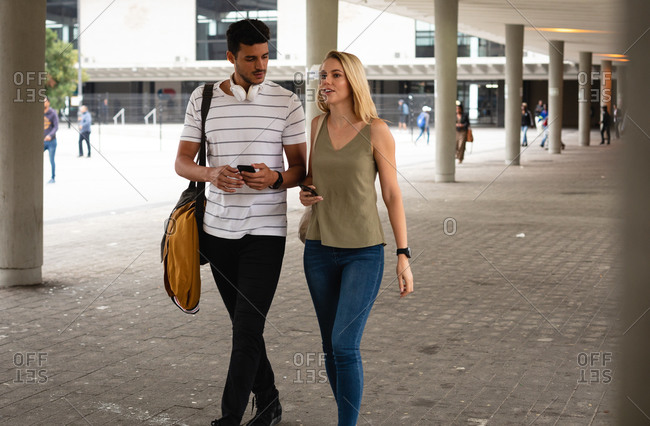 Front view of a Caucasian couple out and about in the city streets during the day, walking, talking and using their smartphones.