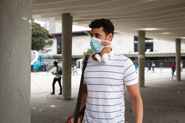 Front view of a caucasian man out and about in the city streets during the day, wearing face mask against air pollution and covid19 coronavirus.