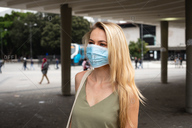 Front view of a caucasian woman out and about in the city streets during the day, wearing face mask against air pollution and covid19 coronavirus..