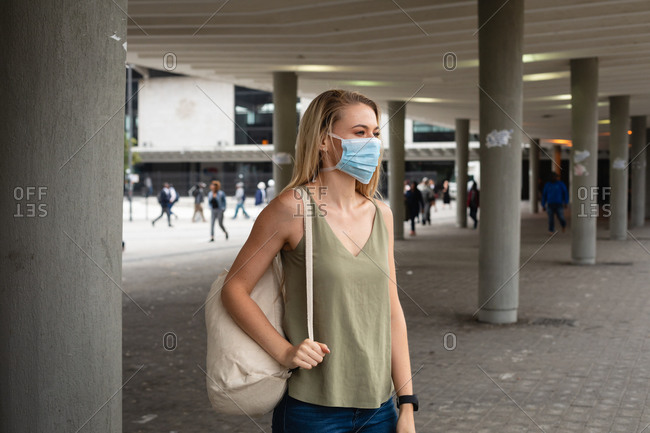 Side view of a caucasian woman out and about in the city streets during the day, wearing face mask against air pollution and covid19 coronavirus.