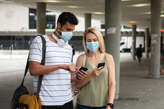 Front view of a caucasian couple out and about in the city streets during the day, wearing face masks against air pollution and covid19 coronavirus, using their smartphones.
