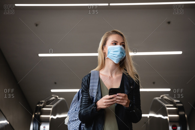 Front view of a caucasian woman with long blind hair, leaving an escalator, using her smartphone and wearing face mask against air pollution and covid19 coronavirus.