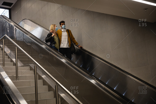 Front low angle view of a caucasian couple out and about in the city, going down in underground station with an escalator, wearing face masks against air pollution and covid19 coronavirus.