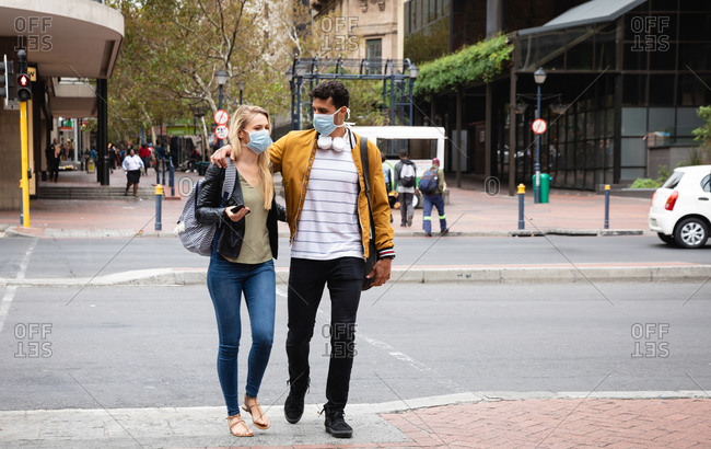 Front view of a caucasian couple out and about in the city streets during the day, wearing face masks against air pollution and covid19 coronavirus.