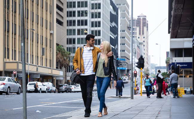 Front view of a happy Caucasian couple out and about in the city streets during the day, embracing and smiling.