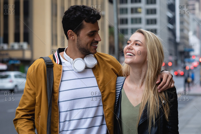 Front view close up of a happy Caucasian couple out and about in the city streets during the day, embracing and smiling.