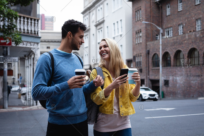 Front view of a happy Caucasian couple out and about in the city streets during the day, holding cups of takeaway coffee, using a smartphone and smiling.
