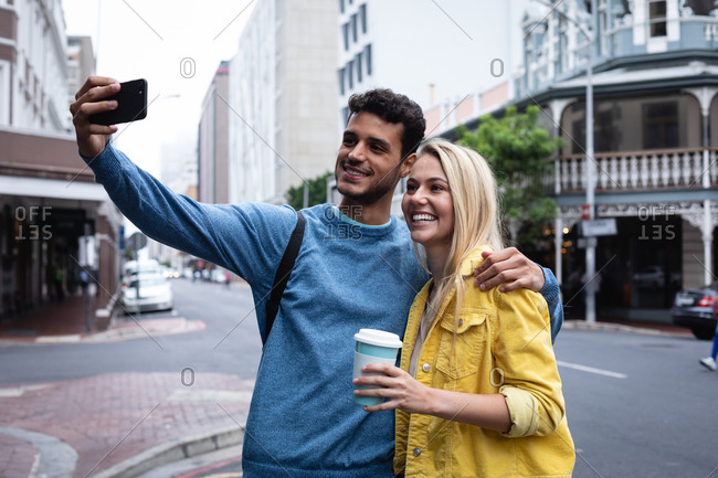 Front view of a happy Caucasian couple out and about in the city streets during the day, embracing while taking a selfie with their smartphone.