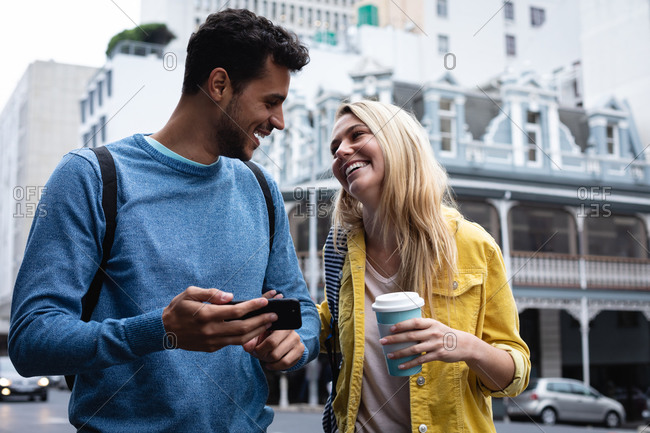 Front view of a happy Caucasian couple out and about in the city streets during the day, holding cup of takeaway coffee, using a smartphone and smiling.