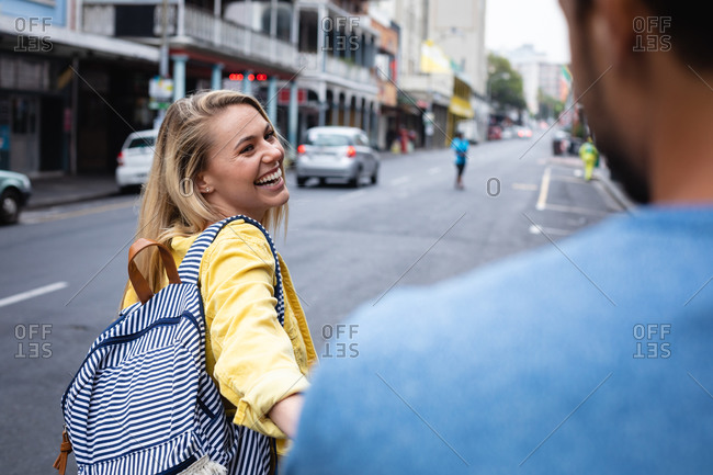Rear view of a happy Caucasian woman with long blond hair, walking through the street, holding a hand of her partner, smiling.