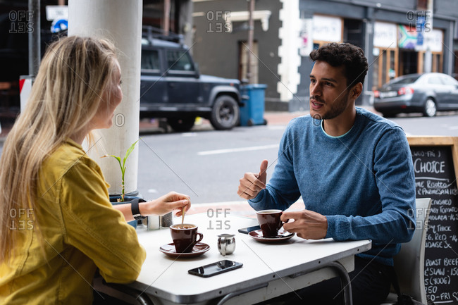 Side view of a Caucasian couple sitting by a table at a coffee terrace, having coffee, talking and enjoying time together.