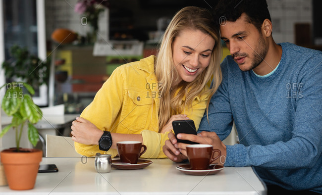 Front view of a Caucasian couple sitting by a table at a coffee shop, having coffee, enjoying time together and using their smartphone.