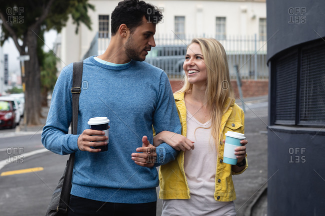 Front view of a happy Caucasian couple on the go in the city, holding takeaway coffee, walking arm in arm, smiling and enjoying time together.