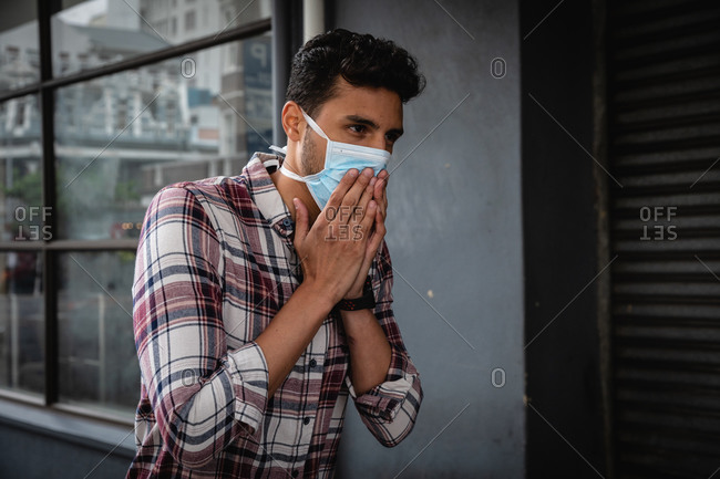 Front view close up of a caucasian man wearing checkered shirt and face mask against air pollution and covid19 coronavirus, walking through the street and covering his face while coughing.