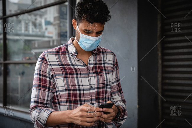 Front view close up of a caucasian man wearing checkered shirt and face mask against air pollution and covid19 coronavirus, walking through the city streets, using his smartphone.