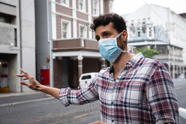 Front view close up of a caucasian man wearing checkered shirt and face mask against air pollution and covid19 coronavirus, hailing a taxi in the street.