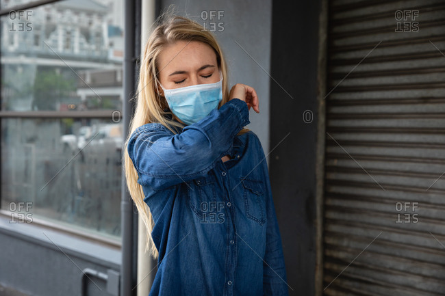 Front view close up of a caucasian woman wearing face mask against air pollution and covid19 coronavirus, walking the street and covering her face while coughing.