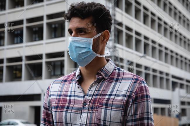 Front view close up of a caucasian man wearing checkered shirt and face mask against air pollution and covid19 coronavirus, walking through the city streets.