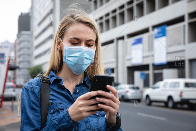 Front view close up of a caucasian woman wearing face mask against air pollution and covid19 coronavirus, walking through the city streets, using her smartphone.