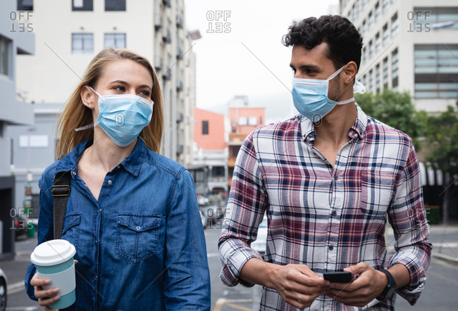 Front view close up of a caucasian couple wearing face masks against air pollution and covid19 coronavirus, holding cop of takeaway coffee, using a smartphone.