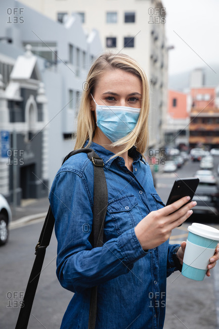 Front view close up of a caucasian woman wearing face mask against air pollution and covid19 coronavirus, walking through the city streets, using her smartphone and holding a cup of takeaway coffee.