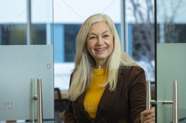 Smiling businessman opening door in office