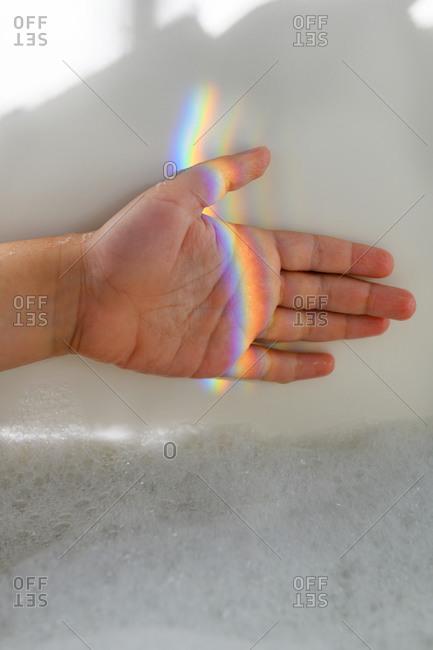 Girl's hand in rainbow light beam in bubble bath