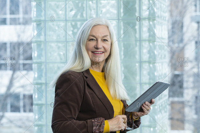 Smiling businesswoman with digital tablet in office