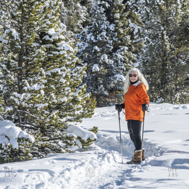Senior woman in orange jacket with hiking poles in snow