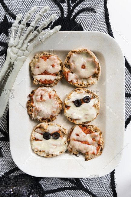 Plate of mini pizzas and hand of Halloween skeleton