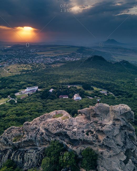 Aerial view of valley from Eagle rocks with a man standing on the top in breathtaking moment of sunset, Pyatigorsk, Russia.