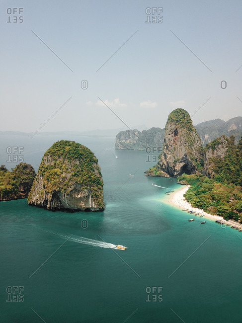 Aerial view of a boat exploring the Limestone Cliffs and white sand beaches in the sea in Krabi, Southern Thailand
