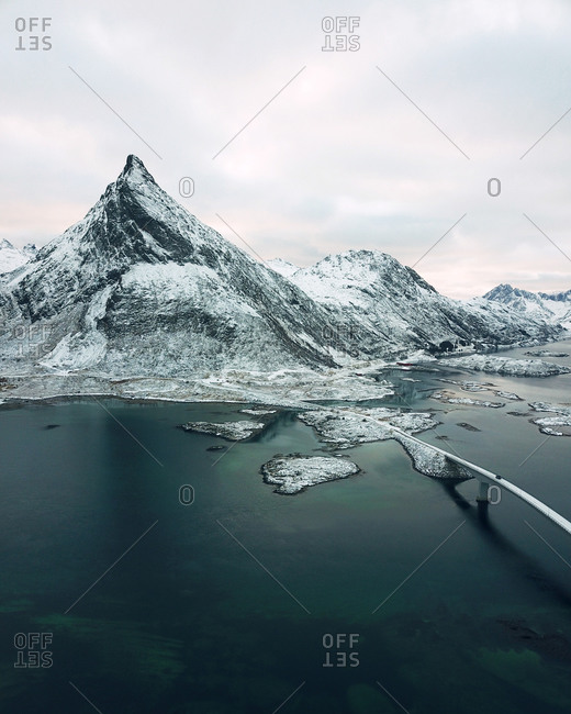 Aerial view of iconic Fredvang Bridges and snowy mountains, Lofoten Islands, Northern Norway in the Arctic Circle