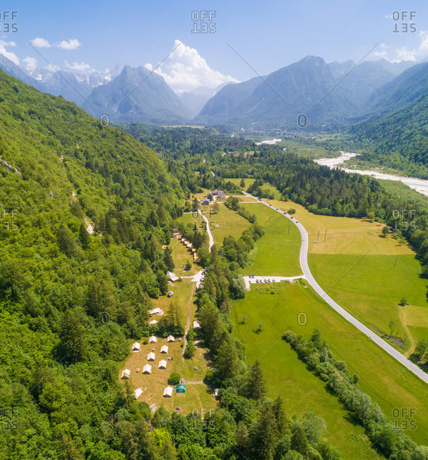 Aerial view of a pine forest with mountains in the background in Bovec, Slovenia