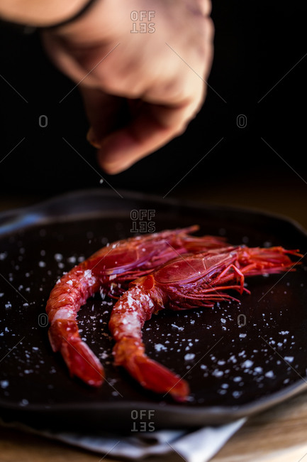 Chef sprinkling salt over red prawns red prawns on a plate