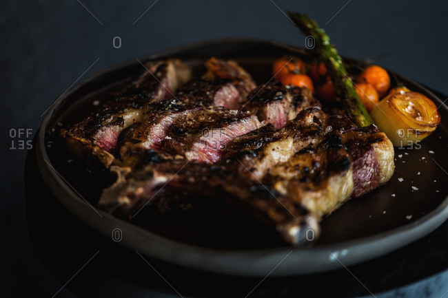 Grilled juicy meat served with veggies