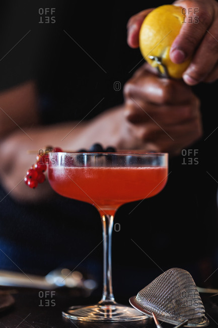 Bartender adding zest to a cocktail garnished with berries