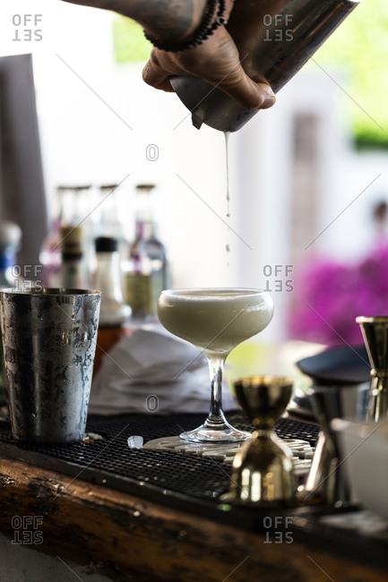 Bartender pouring cocktail into a coupe glass