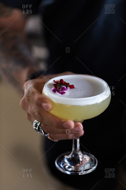 Hand holding a foamy cocktail in a coupe glass