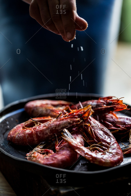 Hand sprinkling salt over red prawns red prawns on a plate