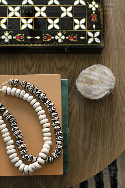 Handmade bead necklaces on a wooden table by a fancy board game