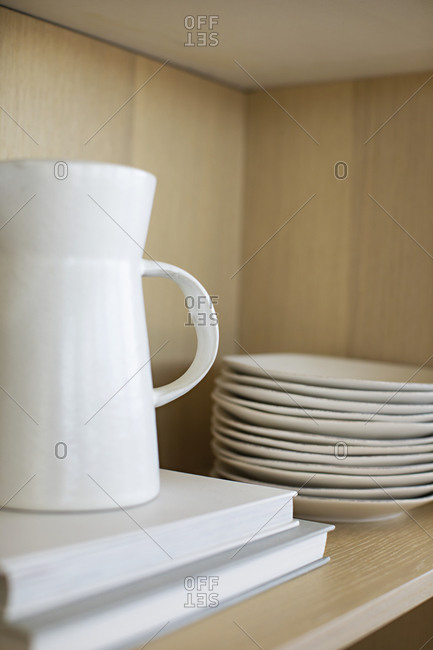White pitcher on books beside a stack of plates