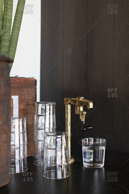 Glasses stacked by bar faucet