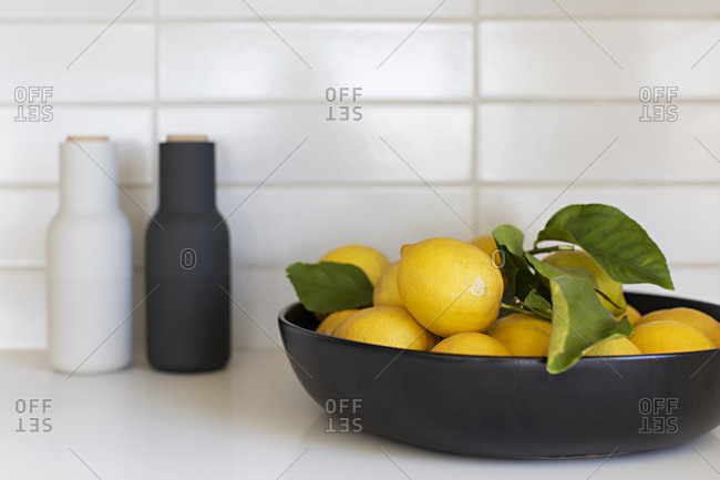 Lemons in a black bowl on white counter by salt and pepper shakers