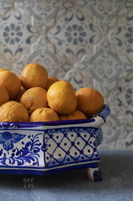 Oranges in a fancy blue bowl