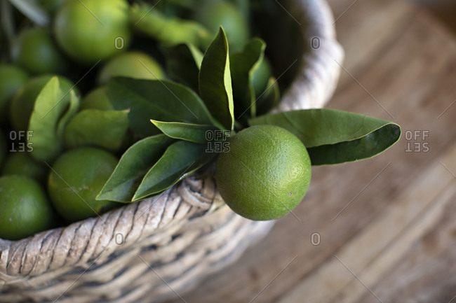 Lime with leaves hanging out of a basket