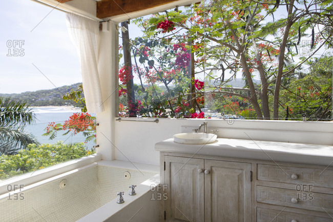 Spa like bathroom overlooking tropical landscape