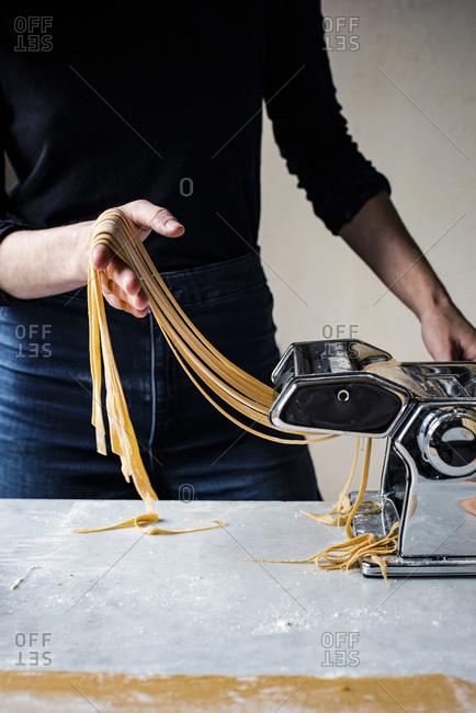 Woman Making Fresh Pasta in a kitchen